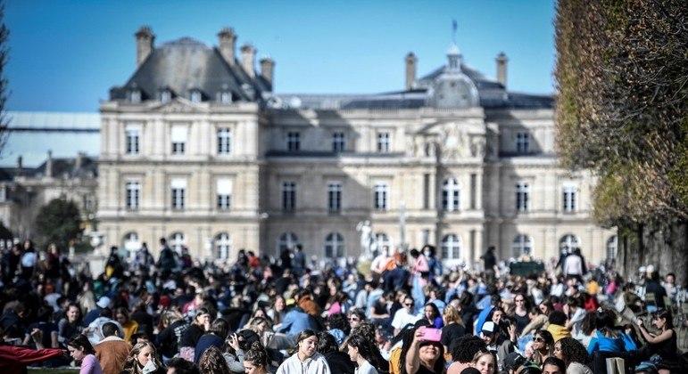 Dezenas de pessoas se reúnem em frente ao Jardin du Luxembourg, em Paris, neste domingo