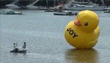 Pato inflável gigante surge próximo a porto com a palavra 'alegria'