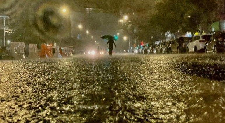 Pedestre tenta passar por alagamento no bairro do Bronx, na cidade de Nova York.