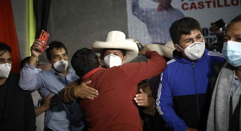Pedro Castillo (centro) é abraçado por apoiador em seu comitê na cidade de Cajamarca