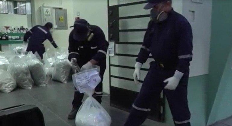 Policiais pesam sacos com drogas antes da incineração