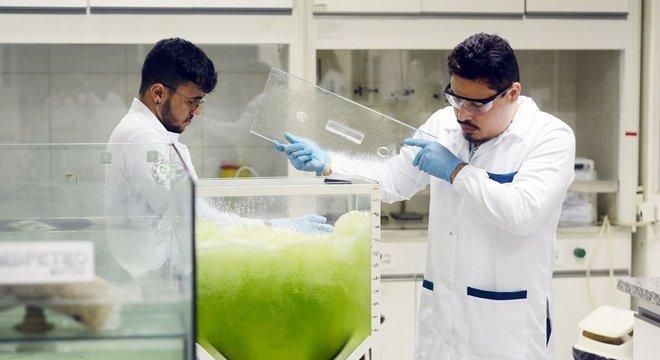 Pesquisadores em laboratório manuseiam um tanque cheio de água contaminada