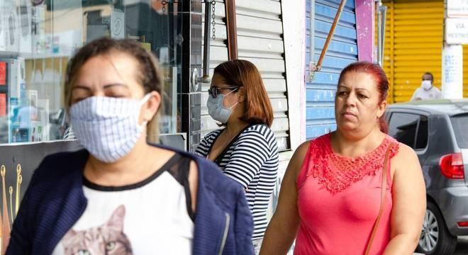 Pessoas com e sem máscara caminham em rua comercial de São Miguel Paulista