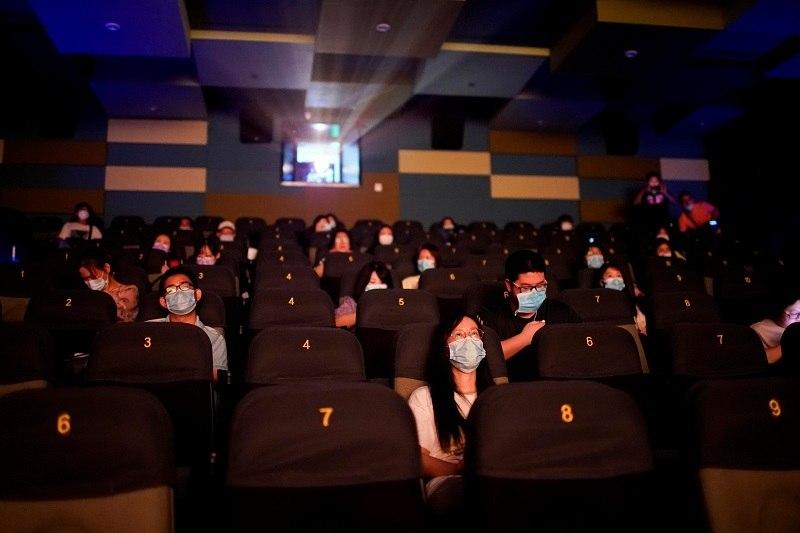 Pessoas de máscara em cinema que reabriu nesta segunda-feira (20) em Xangai