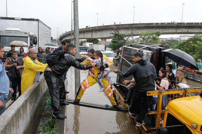 Pessoas são resgatadas em meio ao alagamento na Marginal Tietê, na altura da Ponte das Bandeiras, na manhã desta segunda-feira, 10. (FÁBIO VIEIRA/ESTADÃO CONTEÚDO)