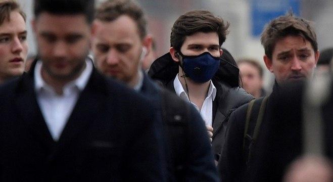 Pessoas utilizam máscara de proteção em Londres