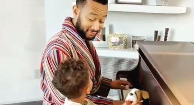 Pai e filho tocam piano juntos enquanto a mãe filma a criança se divertindo