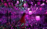 Uma garota admira e interage com uma bela exposição de arte digital do teamLab Planets em Tóquio