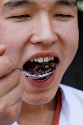 Os insetos vão dominar o mundo, nem que seja na mesa de todos. Nessa foto, um funcionário público come grilos em uma fazenda de grilos no Quirguistão