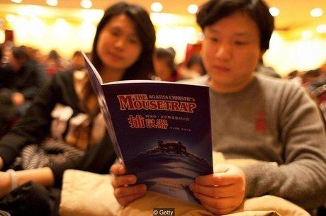 Plateia lê o programa da peça antes de uma apresentação de 'A Ratoeira', de Agatha Christie, no Shanghai Lyceum Theatre