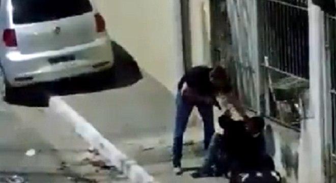 Nas imagens, agente pega homem pela gola da camiseta e o arrasta até muro