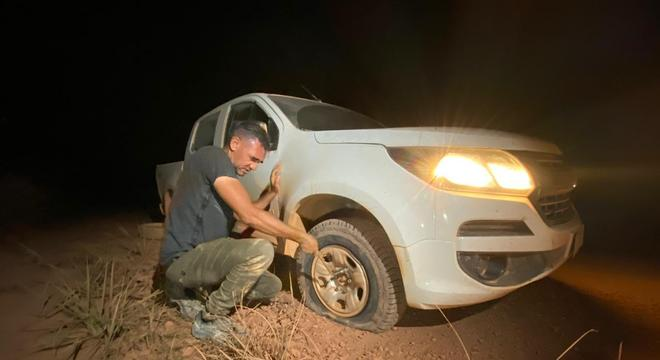 Motorista Didi troca a roda da caminhonete que leva a equipe da Record TV