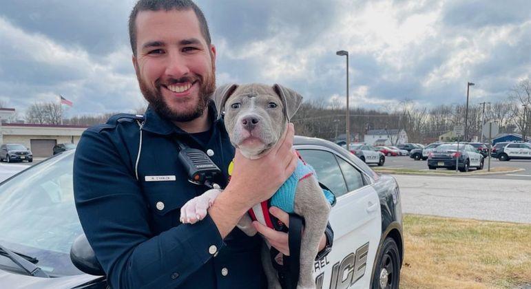 Policial segura o pequeno cachorro que ele resgatou em serviço