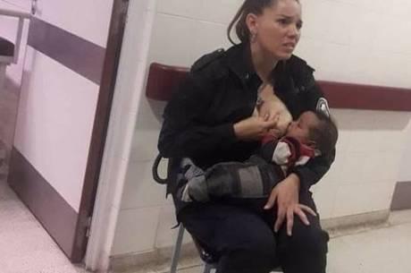 Policial, ainda fardada, amamentando um bebê em hospital