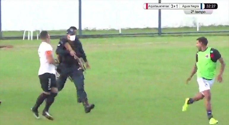 Policial, com a arma em mãos, corre atrás de jogador do Águia Negra