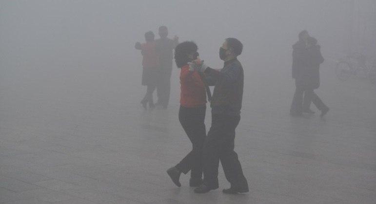 Casais dançam em meio à poluição usando máscaras na China