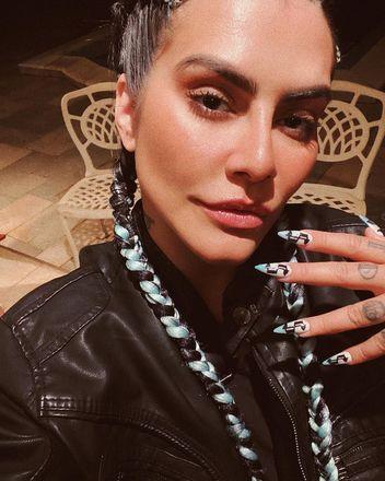 Para combinar com as tranças, a atriz usou um tom de azul claro nas pontas da unha e desenhou um cifrão em todas elas