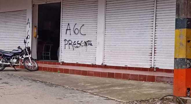 Outra fachada pichada com a sigla do grupo paramilitar AGC na Colômbia