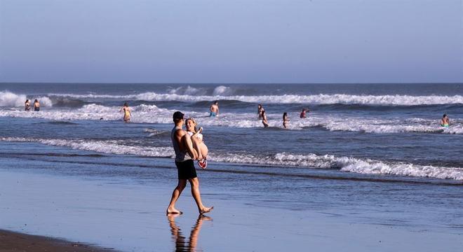 Casal se diverte na praia de Huntington Beach, na California, nos Estados Unidos