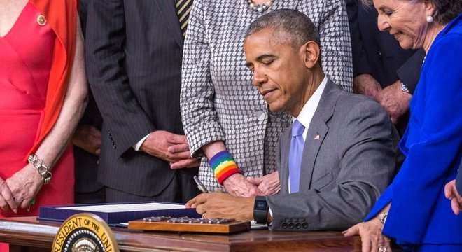 Presidente Barack Obama assinando um projeto de lei com a mão esquerda