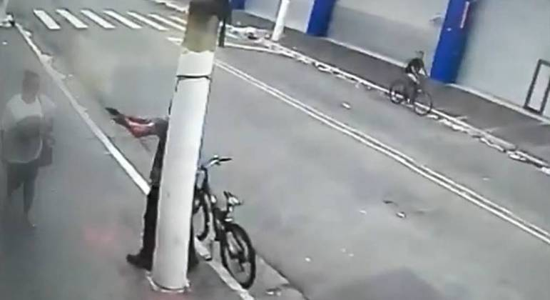 Polícia investiga a participação de um terceiro suspeito, que aparece ao fundo em uma bicicleta