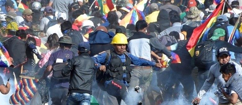 Manifestantes fogem do gás lacrimogêneo durante os confrontos com a polícia em Sacaba