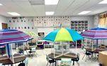 Outra sala de aula resolveu implantar a temática praiana, com guarda-sóis e divisórias em cada mesa