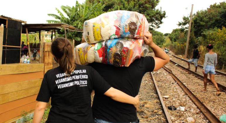 Juliana, o marido e outros voluntários entregam os kits nas moradias à beira dos trilhos de trens