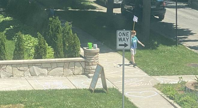 Aiden andando pela calçada desenhada com sua placa de protesto