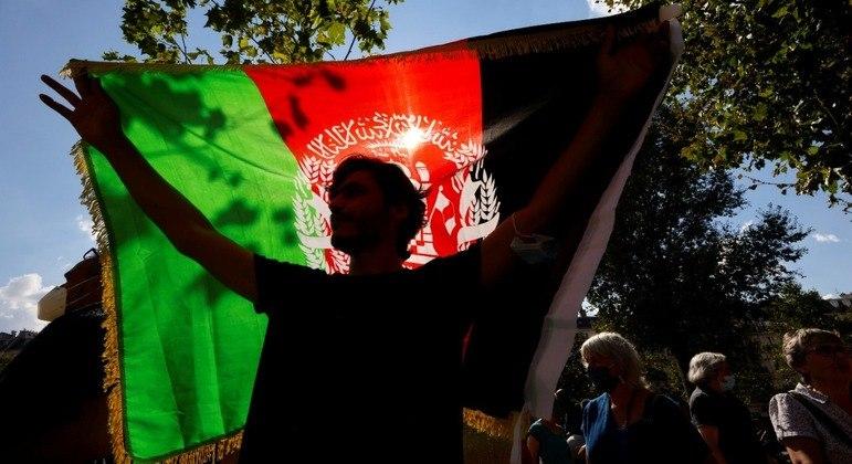Manifestante afegão segura bandeira do Afeganistão durante protesto em Paris