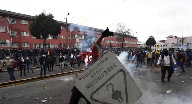 Manifestante usa placa de rua como escudo; ao fundo está a maternidade