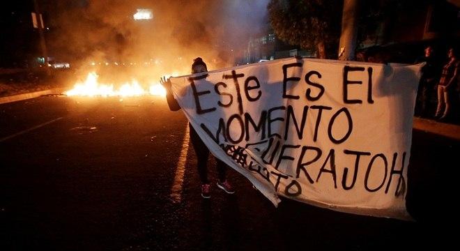 Manifestantes seguram uma bandeira durante um protesto contra o governo de Honduras