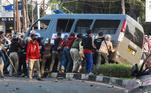 Manifestantes tombam ônibus da polícia durante manifestação em Jacarta, Indonésia, contra mudanças na legislação trabalhista