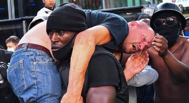 Patrick Hutchinson carrega manifestante para fora de confusão no sábado