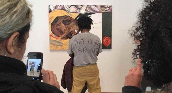O artista Parker Bright protestou contra a pintura de Dana Schutz de uma vítima de linchamento ao obstruir a visão da obra (Crédit: Twitter)