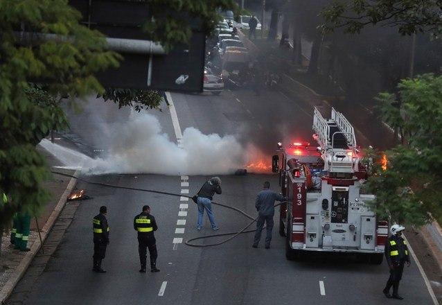 Bombeiros tentam controlar fogo em avenida do centro de São Paulo durante manifestação contra a Reforma da Previdência nesta sexta-feira (14)