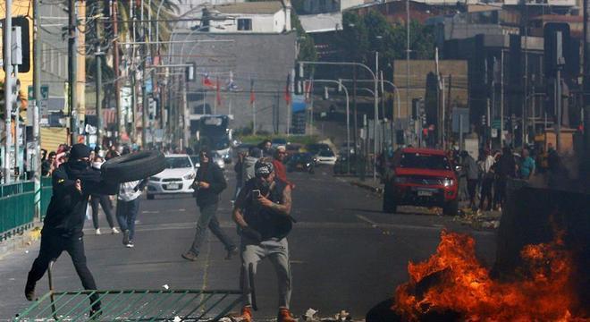 Manifestantes chilenos protestam em frente ao Congresso neste domingo (20)