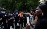 Mulher negra encara fila de policiais em Nova York, durante protestos contrao racismo e a violência policial após a morte de George Floyd