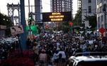 Manifestantes em Nova York passam por placa luminosa que adverte 'Distanciamento social necessário', durante ato contra o racismo e a violência policial após a morte de George Floyd
