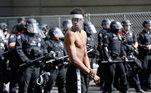 Manifestante em Portland, Oregon, usando máscara de proteção em frente a uma fila de policiais durante manifestações contra o racismo e a violência policial após a morte de George Floyd