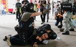 Policial aponta pistola de gás de pimenta enquanto outro imobiza no chão um homem que protesta contra a nova Lei de Segurança Nacional de Hong Kong