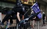 Manifestante pula grade de proteção durante protestos contra a nova Lei de Segurança Nacional de Hong Kong