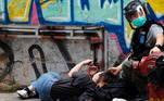 Um mulher ferida é vigiada por uma policial durante os protestos contra nova Lei de Segurança Nacional de Hong Kong