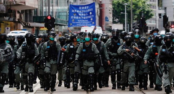 Policiais de Hong Kong com cartaz avisando que aplicarão nova Lei de Segurança Nacional