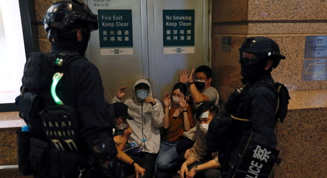 Dois policiais cercam um grupo de manifestantes detidos em protestos em Hong Kong