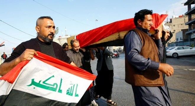 Manifestantes carregam caixão de homem morto por forças policiais do Iraque