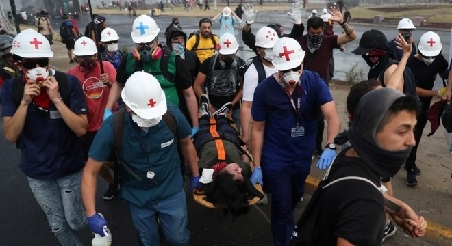 Civis carregam manifestante ferido em meio aos protestos de outubro no Chile