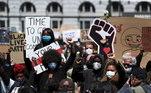 Pessoas com cartazes e punhos cerrados durante protesto contra o racismo em Bruxelas