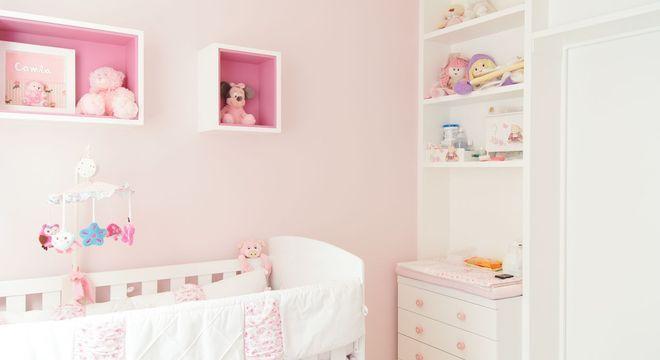 quarto infantil em tons de rosa com nichos de madeira