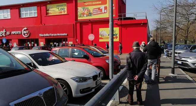Italianos formam filas na porta de supermercados da Lombardia